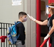 A student has his temperature taken before entering PS 179 elementary school in the Kensington neighborhood, Tuesday, Sept. 29, 2020, in the Brooklyn borough of New York. Hundreds of thousands of elementary school students are heading back to classrooms Tuesday as New York City enters a high-stakes phase of resuming in-person learning during the coronavirus pandemic. (AP Photo/Mark Lennihan)