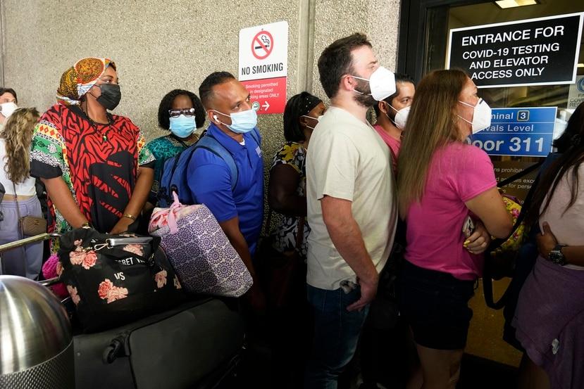 Pasajeros aguardan para recibir pruebas de COVID-19 antes de entrar a un aeropuerto en Fort Lauderdale, Florida.