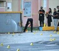 Agentes en la escena del crimen donde se ocuparon sobre 1,000 casquillos de bala.