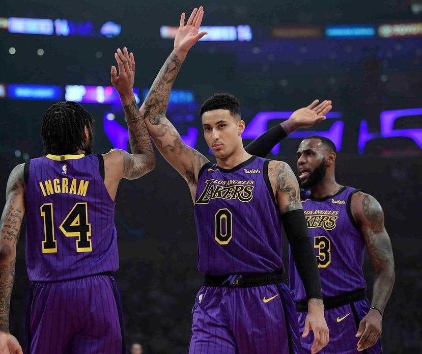El jugador de los Lakers de Los Ángeles Brandon Ingram (izquierda) recibe la felicitación de sus compañeros Kyle Kuzma (centro) y LeBron James tras anotar una canasta en la primera mitad del juego el 23 de noviembre de 2018, en Los Ángeles. (AP/Mark J. Te
