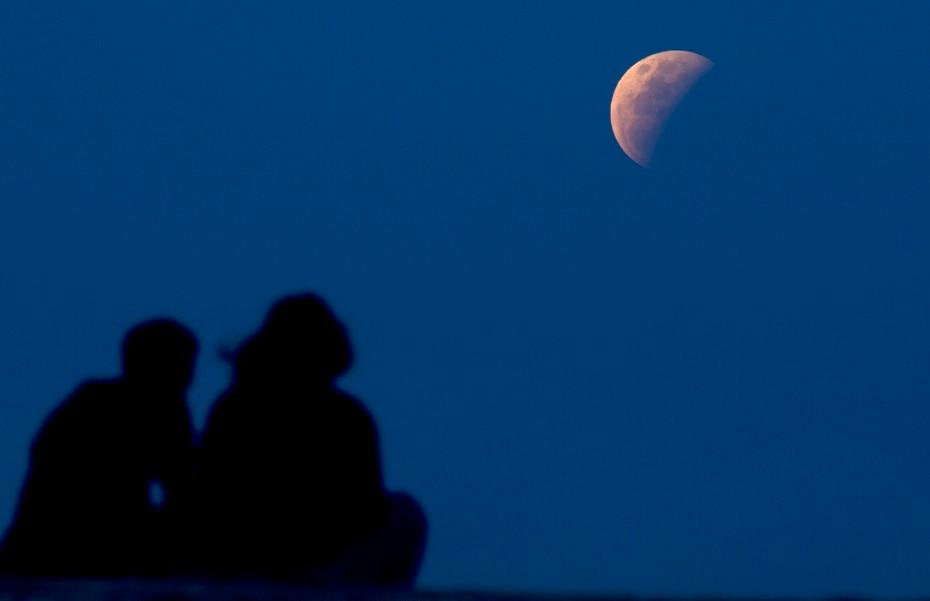 Una pareja en Sanur, Bali, localidad de Indonesia, observa el eclipse.