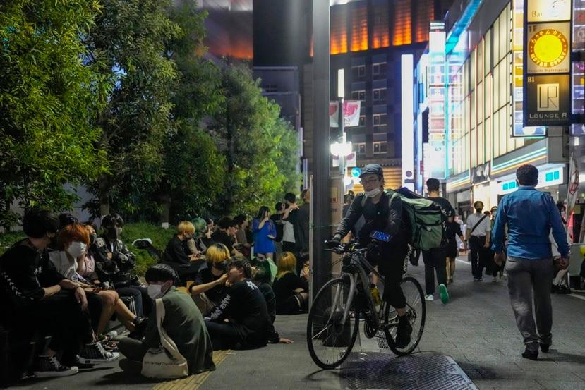 Un grupo de personas se reúne frente a un bar de Tokio que vende bebidas alcohólicas después de las ocho de la noche, a pesar de que las autoridades pidieron que dejasen de hacerlo para combatir la propagación del coronavirus durante los Juegos Olímpicos.