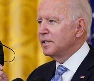 El presidente Joe Biden sostiene una mascarilla mientras habla sobre unas medidas nuevas relacionadas con el coronavirus para los trabajadores federales.