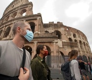 Las personas utilizan una mascarilla para prevenir contagios mientras caminan por al frente del Coliseo en Roma, Italia.