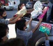 """Los niños reciben regalos de Navidad donados por el grupo de voluntarios """"Un Juguete, Una Buena Noticia"""" desde la parte trasera de una camioneta en Caracas, Venezuela, el viernes 18 de diciembre de 2020. (AP Foto/Ariana Cubillos)"""