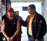 In this photo taken  Sunday, April 18, 2010, Venezuela's former lightweight boxing champion Edwin Valero, left, is escorted by a police officer to a police station in Valencia, some 150 kms, some 93 miles, west of Caracas. Valero committed suicide in his jail cell on early Monday just hours after he was arrested in his wife's killing, police said.  (AP Photo/Edsau Olivares /Notitarde)