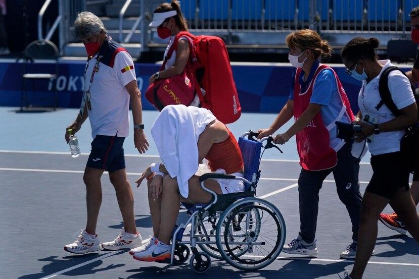 La española Paula Badosa sale de la cancha en una silla de rueda tras sentirse indipuesta durante un partido de cuartos de final del torneo de tenis de los Juegos Olímpicos de Tokio.
