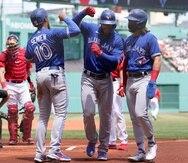 Teoscar Hernández (centro derecha) festeja con Marcus Semien (10) y Bo Bichette tras batear un jonrón ante los Red Sox de Boston.