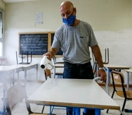 A man disinfects desks in a classroom so as to prevent the spread of COVID-19, at the Melissa Bassi school in Rome, Monday, Aug. 31, 2020. Despite a spike in coronavirus infections, authorities in Europe are determined to send children back to school. They want to narrow learning gaps between haves and have-nots that deepened during virus lockdowns – and to get their parents back to work. (Cecilia Fabiano/LaPresse via AP)