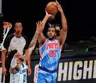 El pivot de los Nets de Brooklyn LaMarcus Aldridge lanza el balón sobre el alero de los Hornets de Charlotte Miles Bridges.