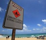 Letrero que advierte de corrientes marinas fuertes en la costa.