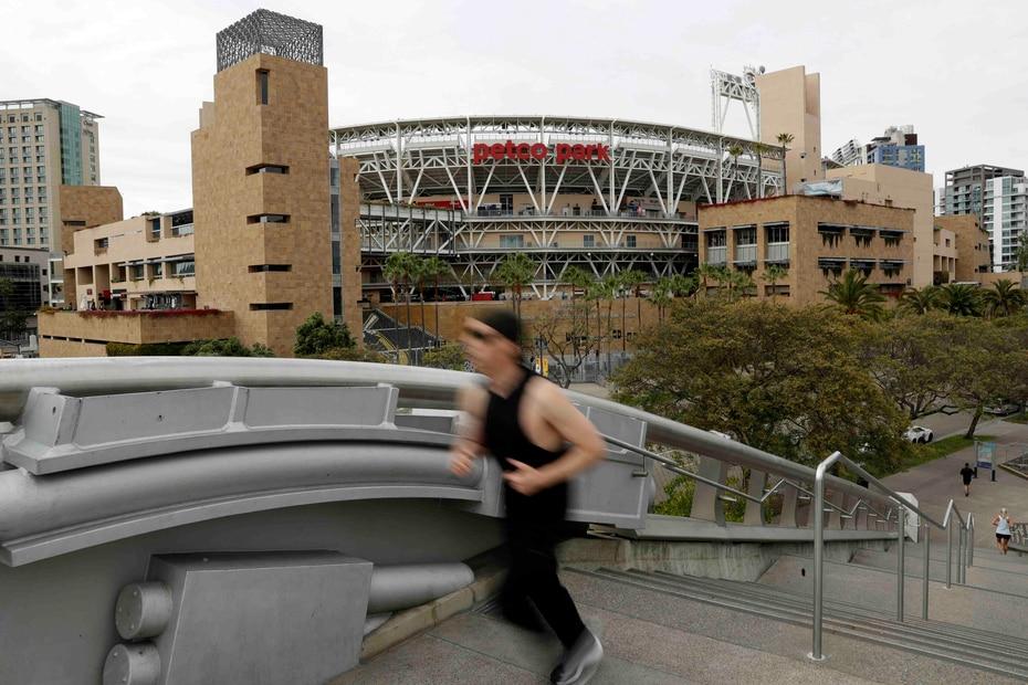 Un corredor pasa frente al Petco Park, hogar de los Padres de San Diego, que debían recibir hoy, 26 de marzo de 2020, a los Rockies de Colorado para su primer juego. (AP/Gregory Bull)