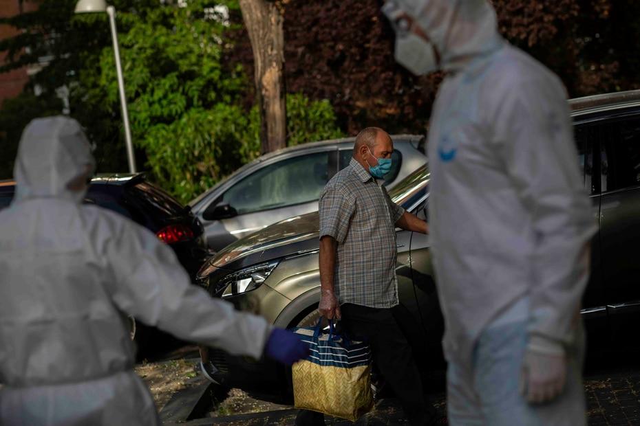 Un hombre con mascarilla pasa junto a miembros de la unidad UVI-6 del Servicio de Urgencias de Madrid (SUMMA) durante el brote de coronavirus, en Madrid.