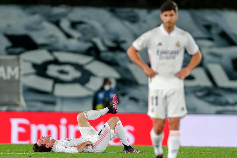 Alvaro Odriozola (en el piso) del Real Madrid busca alivio durante el partido contra el Sevilla.