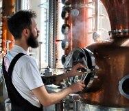 El destilador Sam Garbutt verifica los controles de la destilería en East London Liquor Company en Londres. (AP Photo)