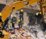 Varios rescatistas buscan víctimas el sábado 27 de marzo de 2021 entre los escombros de un edificio de apartamentos que se vino abajo en el vecindario de el-Salam, en El Cairo, Egipto.