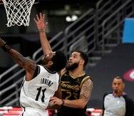 El defensa de los Nets de Brooklyn, Kyrie Irving (11), se levanta para colar un tiro ante Fred VanVleet, de los Raptors de Toronto.
