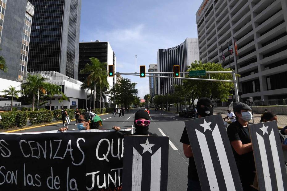 Manifestantes con vestimenta protectora, guantes y máscaras llegaron ante las oficinas de la Junta de Supervisión Fiscal.