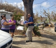 Una residente del barrio Zanjas, de Camuy, recibe suministros de parte de un agente de la DEA.