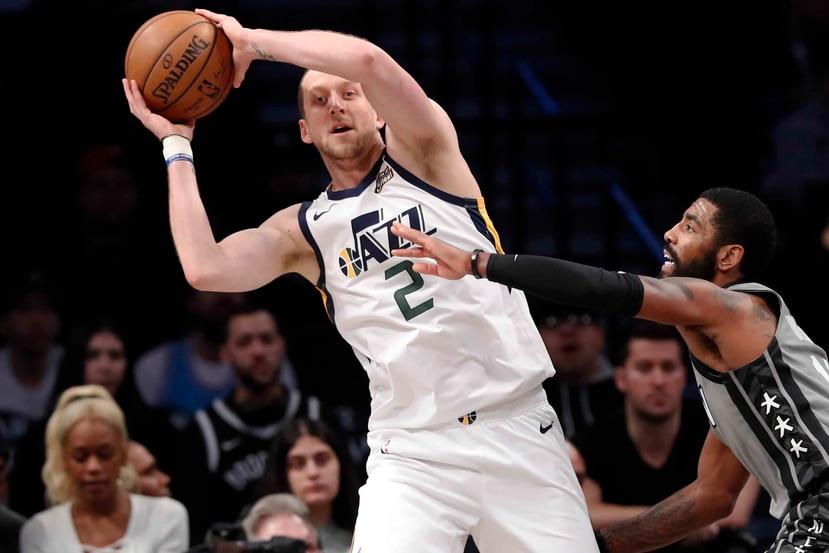 Joe Ingles, alero del Jazz de Utah, busca enviar un pase frente a Kyrie Irving, de los Nets de Brooklyn. (AP / Kathy Willens)