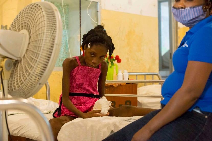 Amazon Annegardine, de 11 años, que recibe tratamiento por niveles anómalos de azúcar en sangre, se sienta en una cama junto a su madre en el Hospital de la Inmaculada Concepción, en Les Cayes, Haití.