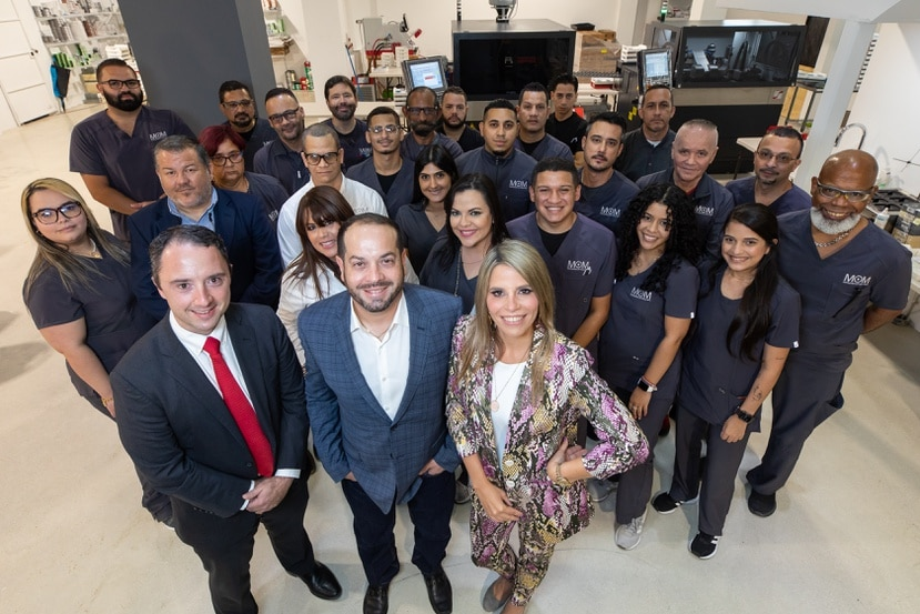 Al frente, en primer plano, Cameron McKenzie, Kenny Vázquez y Claudia Arbona, junto a un grupo de empleados en las instalaciones de la fábrica de lentes en Mayagüez.