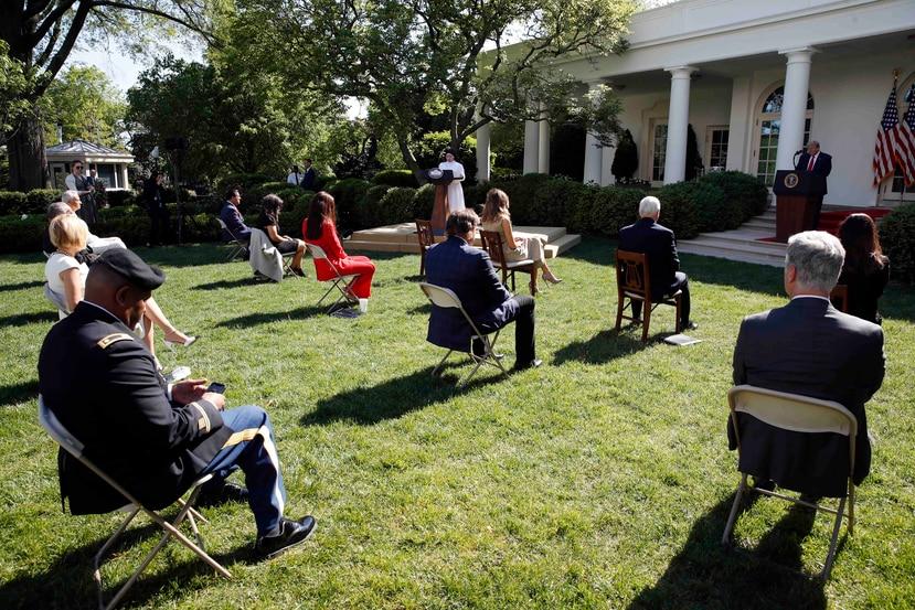 Presidente Donald Trump escucha mientras la hermana Eneyda Martínez, de las Hermanas Pobres de San José, habla durante un oficio en la Casa Blanca, Washington, 7 de mayo de 2020. (AP)