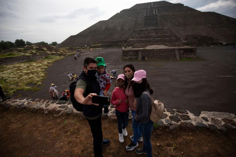 Visitantes se toman una selfie cerca de la Pirámide del Sol en Teotihuacán, México, el jueves 10 de septiembre de 2020, después de la reapertura de este sitio arqueológico tras un cierre de cinco meses a causa de la pandemia del coronavirus.