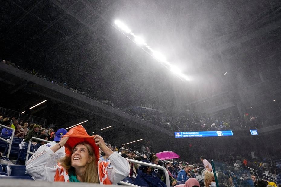 Una mujer se cubre de la lluvia en el estadio Louis Armstrong durante un partido en la segunda ronda del campeonato de tenis del US Open.