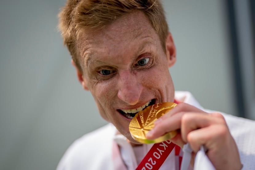 Brad Snyder muerde la medalla de oro que ganó en el triatlón de los Juegos Paralímpicos en Tokio.