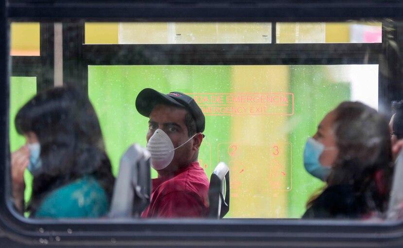 Personas usan mascarillas en un autobús en Ciudad de México. (AP)