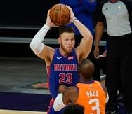 Blake Griffin (23), de los Pistons de Detroit, busca a quién dar un pase ante la marca de Chris Paul, de los Suns de Phoenix, en la primera mitad de un partido de la NBA, el viernes 5 de febrero de 2021.