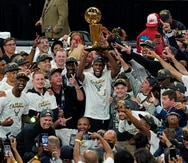 Kris Middleton alza el trofeo de campeonato de la NBA junto a los Bucks de Milwaukee.