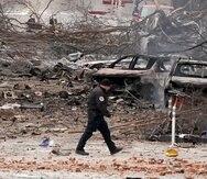 Un oficial camina por la escena de la explosión, donde se aprecian varios vehículos quemados.