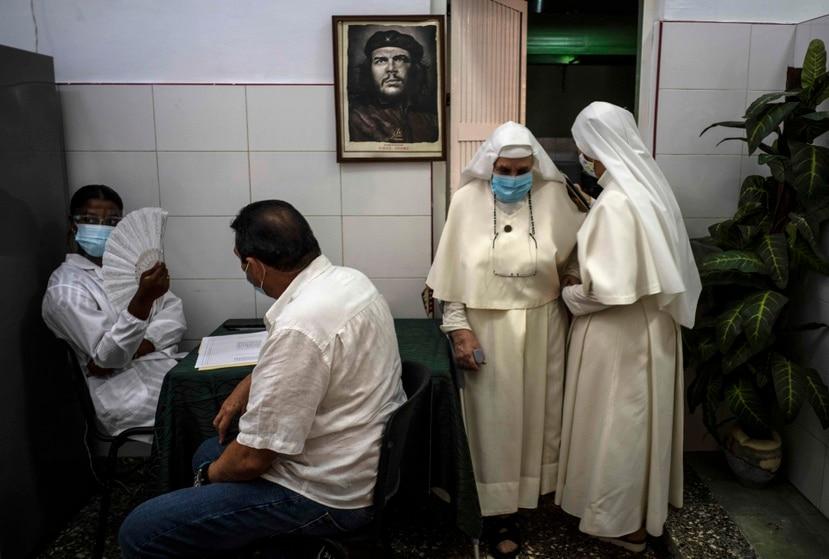 """Un cuadro con la imagen de Ernesto """"Che"""" Guevara cuelga del muro de una habitación de la que dos monjas se retiran tras ser vacunadas contra el COVID-19, el miércoles 23 de junio de 2021, en La Habana, Cuba. (AP Foto/Ramón Espinosa)"""