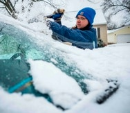 Colleen Streefland quita la nieve de su automóvil durante una nevada el sábado 14 de abril de 2018 en Rochester, Minnesota. (AP)