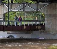 Un par de personas cruza el puente peatonal de Madison Street sobre el Río Clark Fork.
