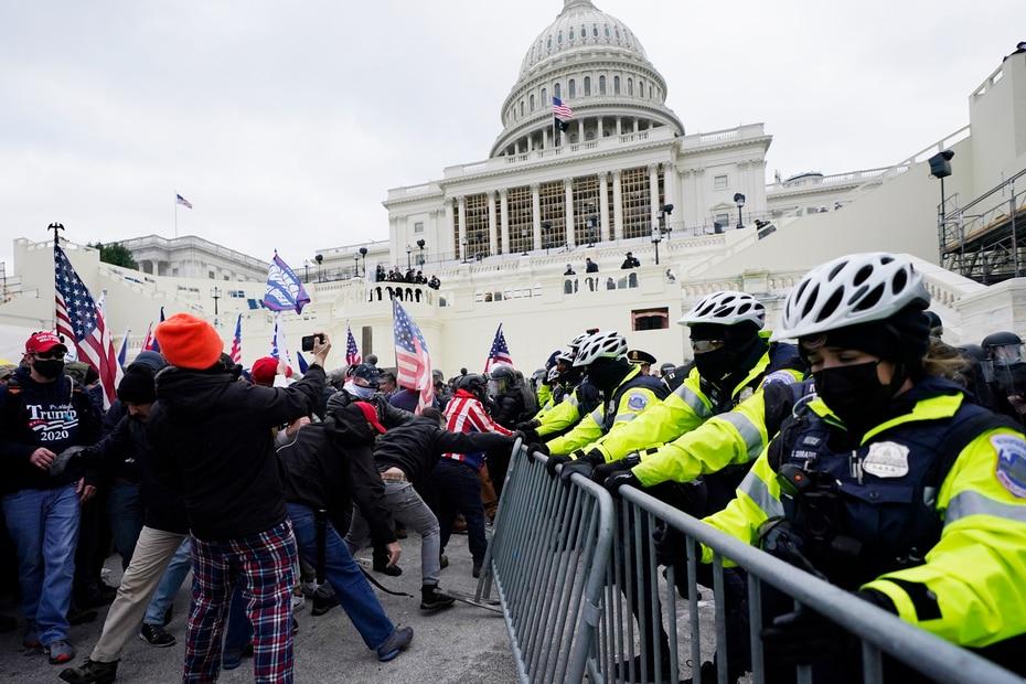 Momento en que los simpatizante de Donald Trump trataban de pasar la barricada de la Policía frente al Capitolio.