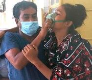 Un hombre asiste a una paciente con dificultad para respirar en el Medical College Hospital, en la ciudad de Rajshahi, en Bangladesh, localidad donde están en aumento los contagios de COVID-19 vinculados a la variante Delta.