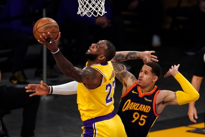 """LeBron James, de los Lakers, realiza un incómodo tiro frente a Juan Toscano-Anderson, de los Warriors, en el partido """"play-in"""" de la NBA."""