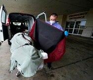 Un empleado de una funeraria cubre el cuerpo de un paciente de COVID-19 que perdió la vida, mientras lo prepara para trasladarlo a la zona de carga, en el Centro Médico Willis-Knighton de Shreveport, Luisiana.