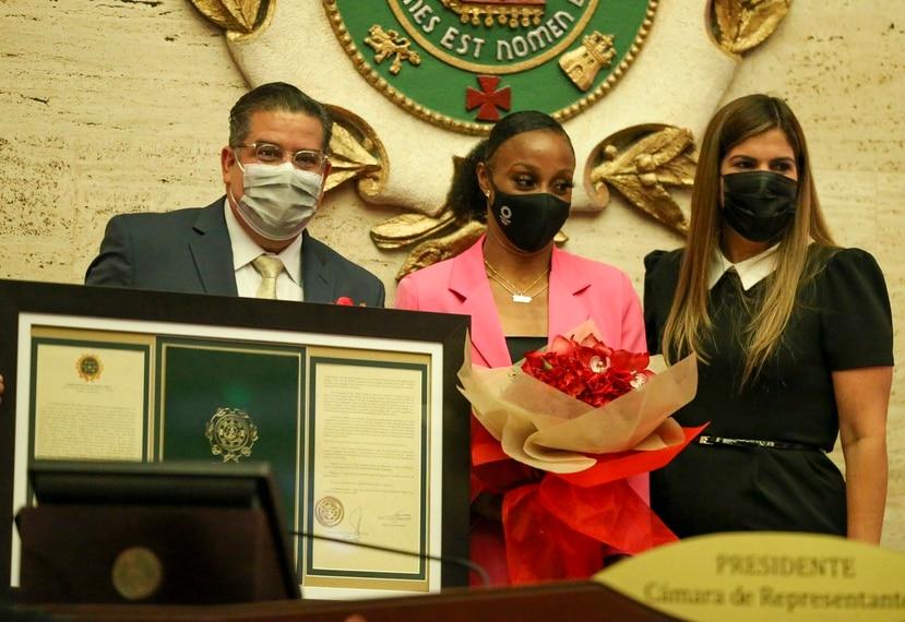 """Jasmine Camacho Quinn fue homenajeada el miércoles en la Legislatura. A la izquierda, el presidente de la Cámara de Representantes, Rafael '""""Tatito"""" Hernández, y a la derecha, la vicepresidenta del Senado, Marially González."""