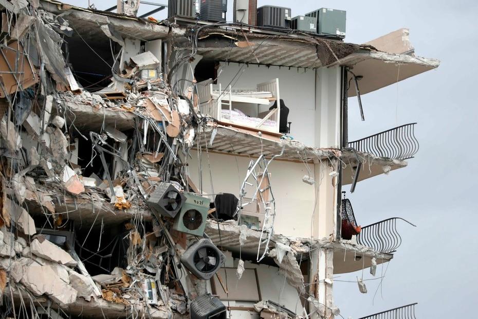 Artículos, consolas de acondicionadores de aire y camas quedan expuestas tras el colapso parcial del condominio Champlain Towers South en Miami.