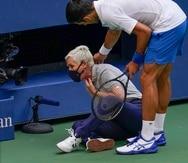 El serbio Novak Djokovic revisa el estado de una jueza de línea a la que asestó un pelotazo en medio de la frustración en el duelo ante el español Pablo Carreño Busta, durante la cuarta ronda del US Open, el domingo 6 de septiembre de 2020, en Nueva York.