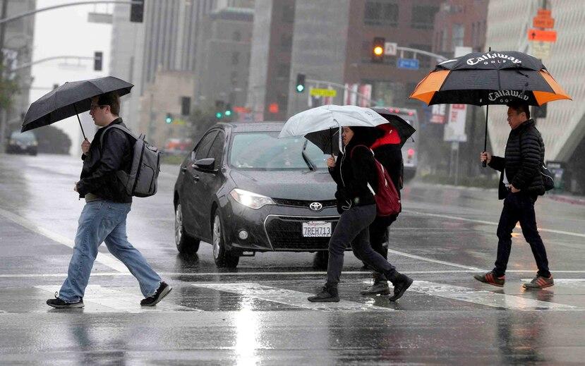 Esta foto de archivo del lunes 6 de febrero del 2017 muestra a peatones cruzando una pista bajo la lluvia en el centro de Los Ángeles. (AP/Nick Ut)