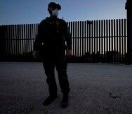 Un agente de la Oficina de Aduanas y Protección Fronteriza monta guardia cerca de una puerta en el muro en la frontera entre México y Estados Unidos durante un operativo de detención de migrantes, en Abram-Perezville, Texas.