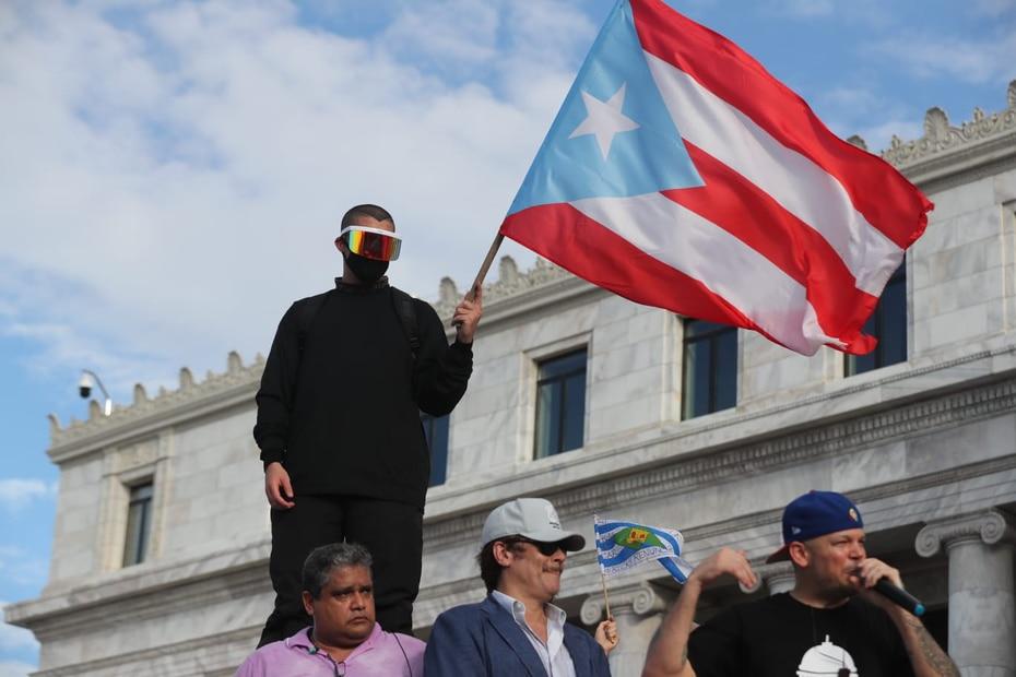 Bad Bunny, vestido de negro y con un enorme visor cubriendo su rostro, sujeta una bandera de Puerto Rico.