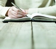 hand writes with a pen in a notebook -----