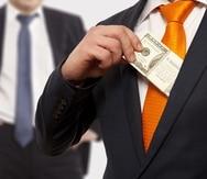Businessman putting money in suit jacket pocket, concept for corruption, bribing