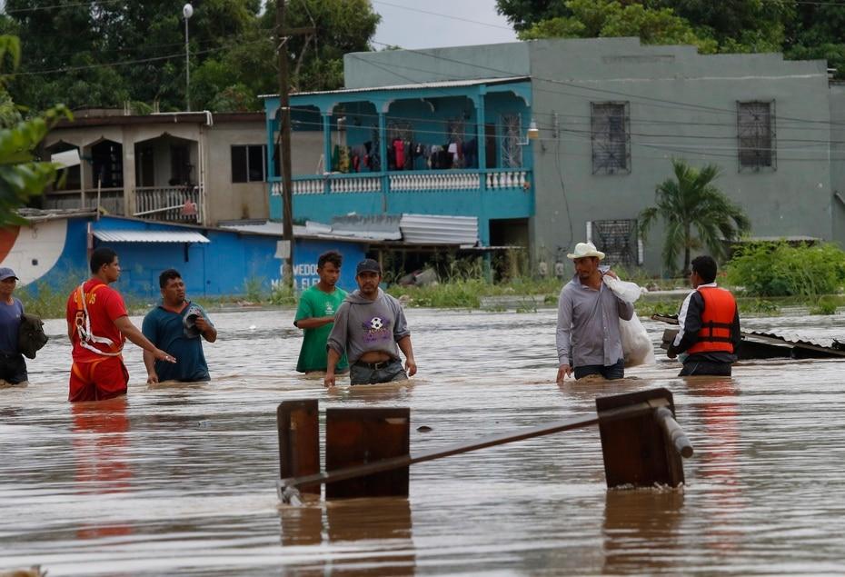 Personas caminan por el área inundada de La Lima, Honduras.